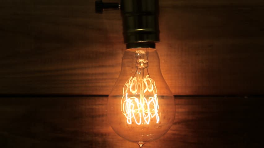 Old Vintage Edison S Light Bulb Glowing On Background Of Wooden Planks Gradually Defocused And Transformed Into Bokeh