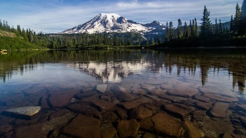 The camera moves across a rock-tile bottomed lake with Mount Rainier reflecting on the water
