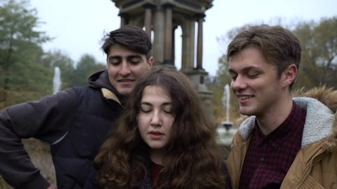 Threesome of friends making selfie together near a fountain. Autumn landscape.