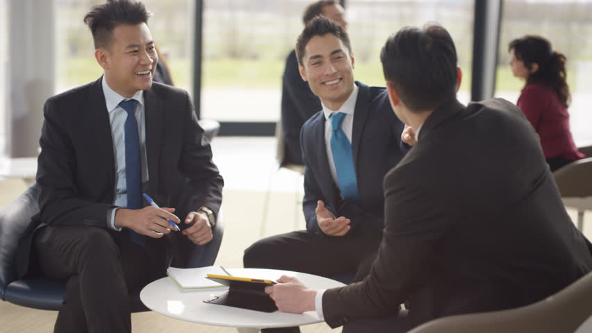 4K Asian businessmen in discussion in busy meeting area of modern office (UK-Oct 2016) #21771307