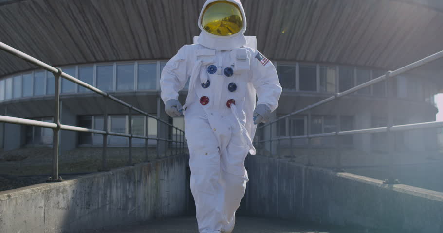 4K Funny astronaut doing a dance as he walks away from mission control building. (UK-Oct 2016)