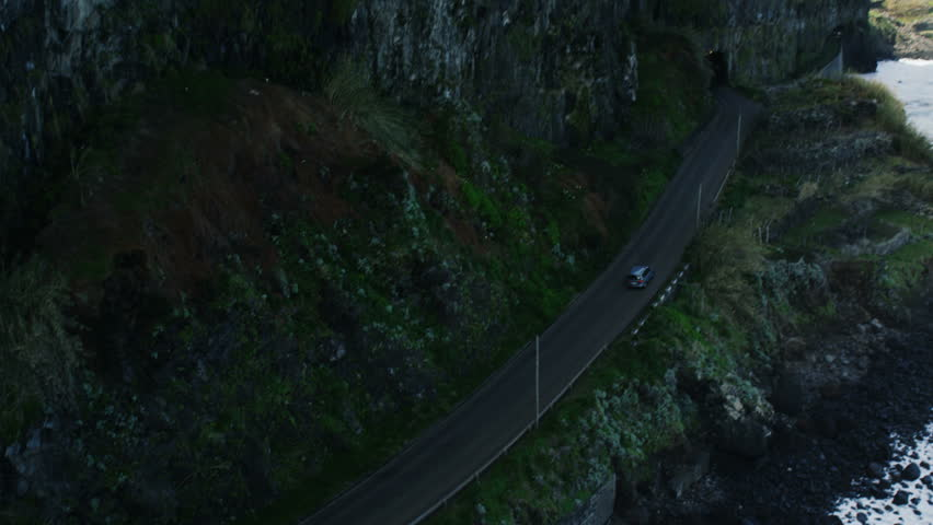 Car Going Near the Sea Along Mountain Slopes. Aerial Shot from Madeira.