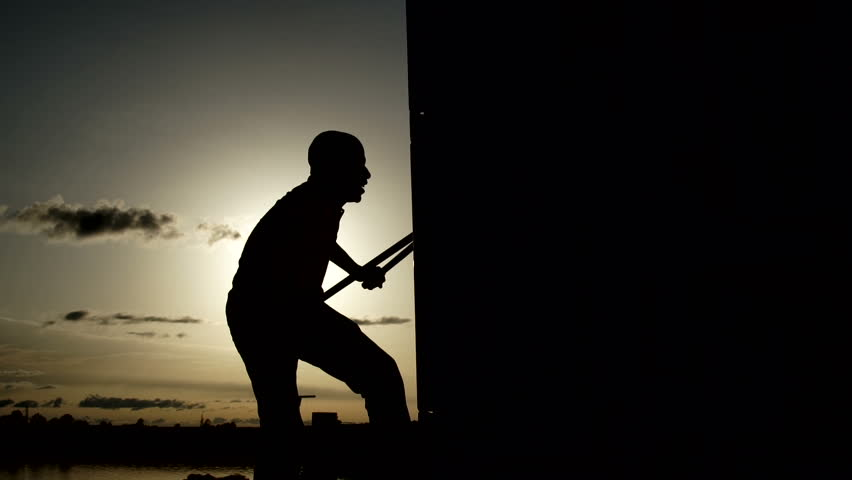 Silohuette of a man opening a container with tongs. Sunset in the background. | Shutterstock HD Video #21830707