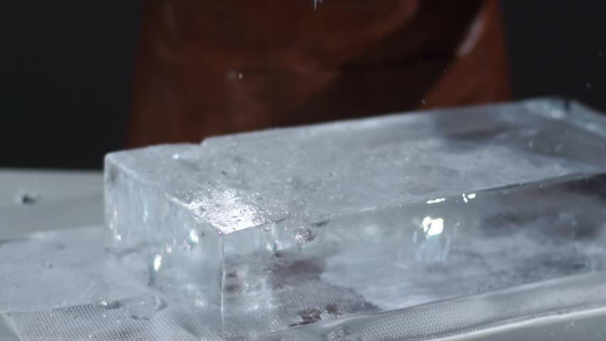 The bartender crushing ice with special fork and breaking off a big piece of ice | Shutterstock HD Video #21835267