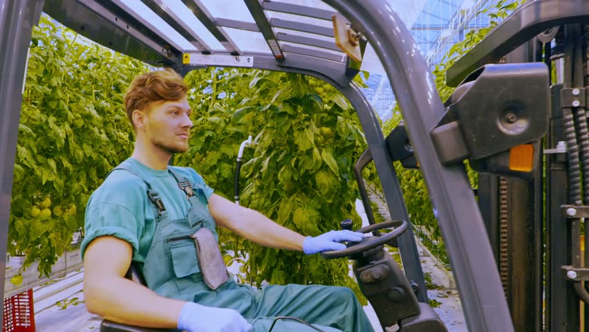 Young attractive man working on electric forklift in greenhouse   Shutterstock HD Video #21837607