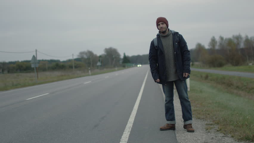 Casualy Dressed Traveler standing by the Highway and Thumbing at a Cloudy Day. Shot on RED Cinema Camera in 4K (UHD).