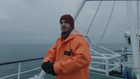 Captain of Commercial Fishing Ship Dressed in Protective Coat Looking through Binoculars. Shot on RED Cinema Camera in 4K (UHD).