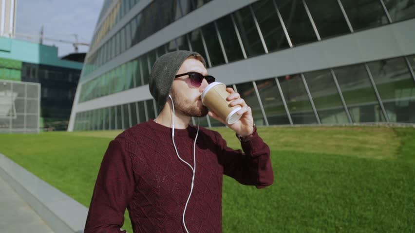 Handsome hipster listening to music in smartphone headphones and drinking coffee from paper cup, walking and dancing | Shutterstock HD Video #21840838