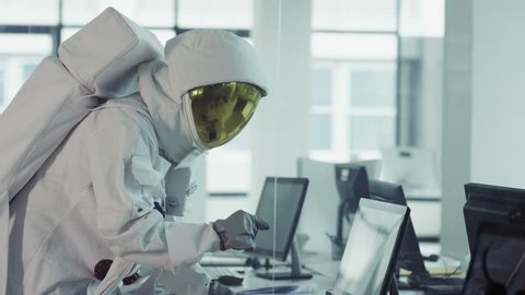 4K Funny astronaut working in room full of computers and doing a little dance (UK-Oct 2016)