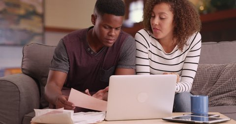 Black millennial couple paying bills with laptop computer in living room. African American man and woman planning investments online in their house. 4k.