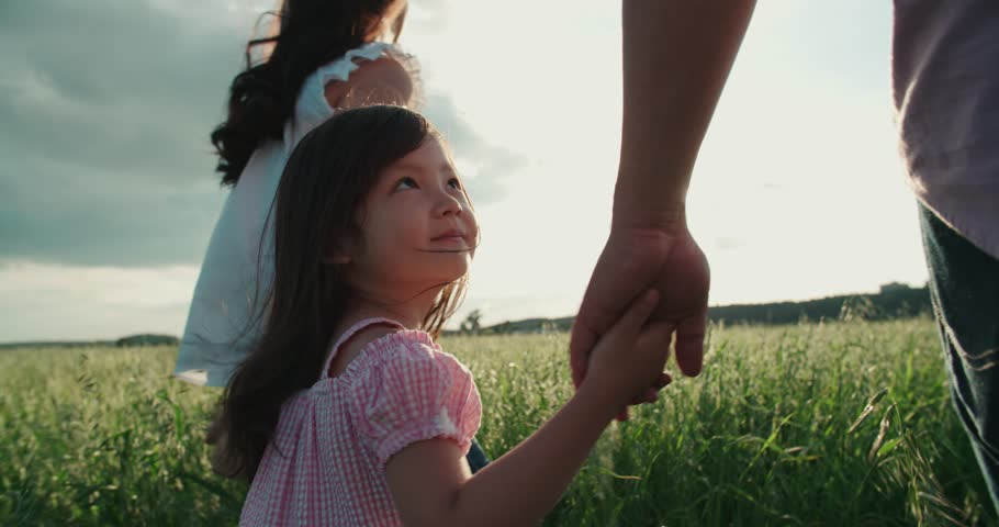little Asian girl walking on the green field with their parents, holding the hand of his father, slow motion