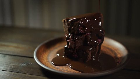 Dark chocolate flowing on brownie cake. Chocolate cake on ceramic plate. Homemade dessert. Chocolate topping on brownie stack.