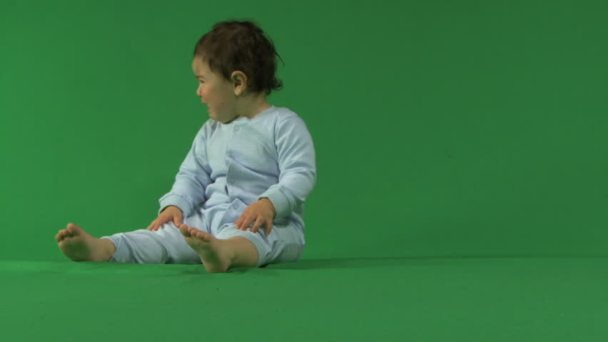 LONG SHOT OF A BABY CRYING ON A GREEN SCREEN