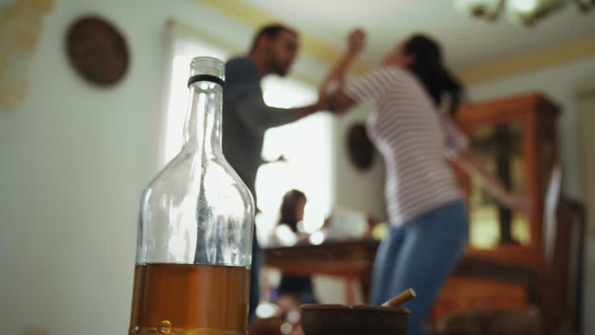 Social issues, abuse and violence on women, young drunk man hitting and beating girl at home after drinking alcohol. Angry husband fighting with abused wife