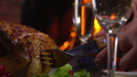 Closeup of a cut piece of chicken on a background of the festive table near the fireplace