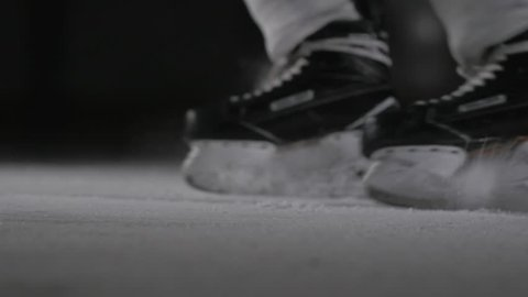 Hockey player make ice sparkles on high speed braking in dark on arena. Motion blur. Legs view only