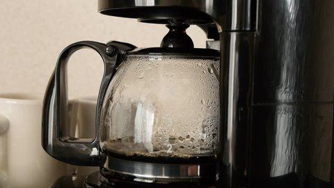 Close-up shot of coffee brewing in coffee maker and flowing in to carafe