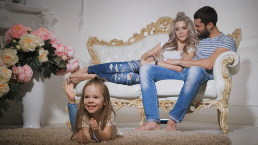 Happy family, expecting new baby, with little smiling girl in the foreground, lying on the carpet, making faces and dangling legs. Her father and pregnant mother sitting together