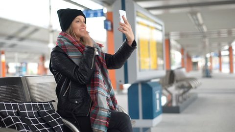 Happy girl having a videocall on smartphone while sitting on a platform