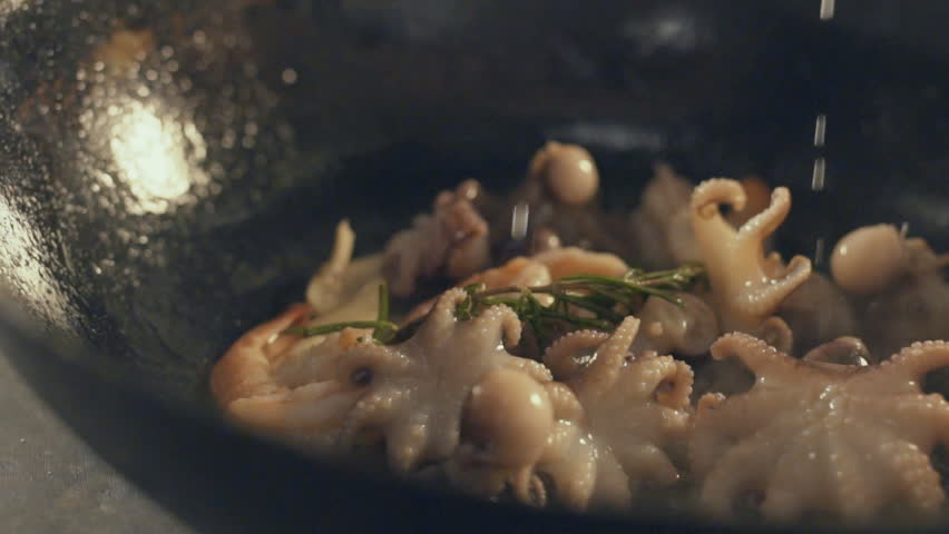 Chef is cooking seafood dish