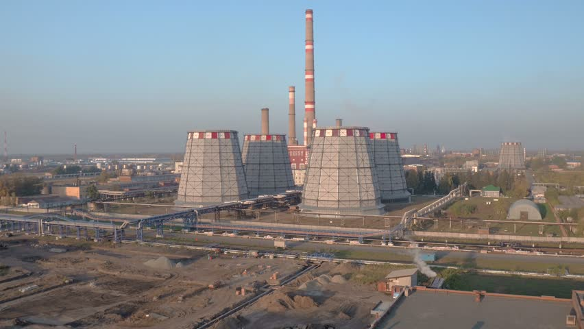 Aerial shot huge cooling towers of brown coal power plant at background of industrial landscape