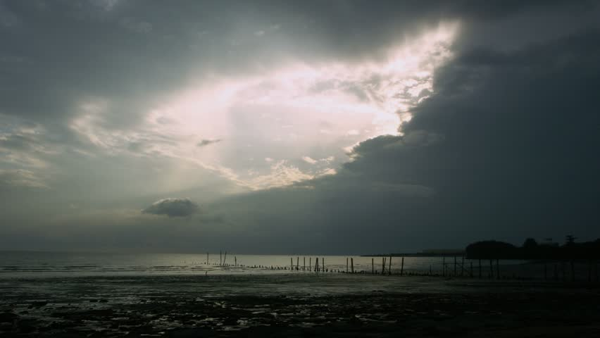 Timelapse of sunset by beach with old pier, Malacca, Malaysia.