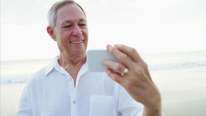Fit Caucasian senior man smartphone technology selfie video diary social media traveler healthcare beach  | Shutterstock HD Video #22063297