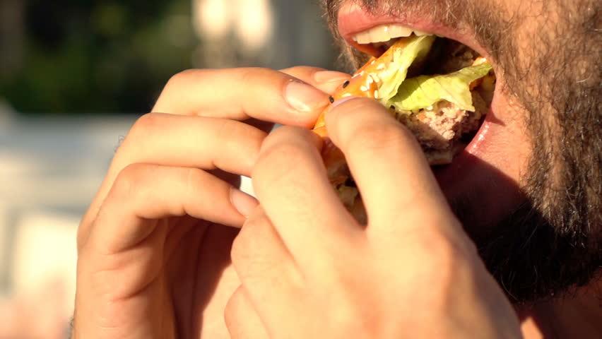 Close up of man eating burger, super slow motion 240fps