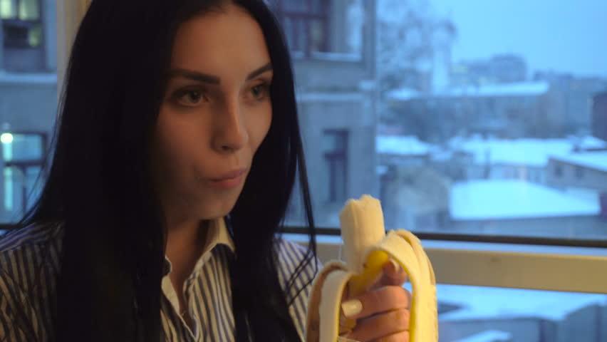 close up of sexy young girl with dark hair eats banana