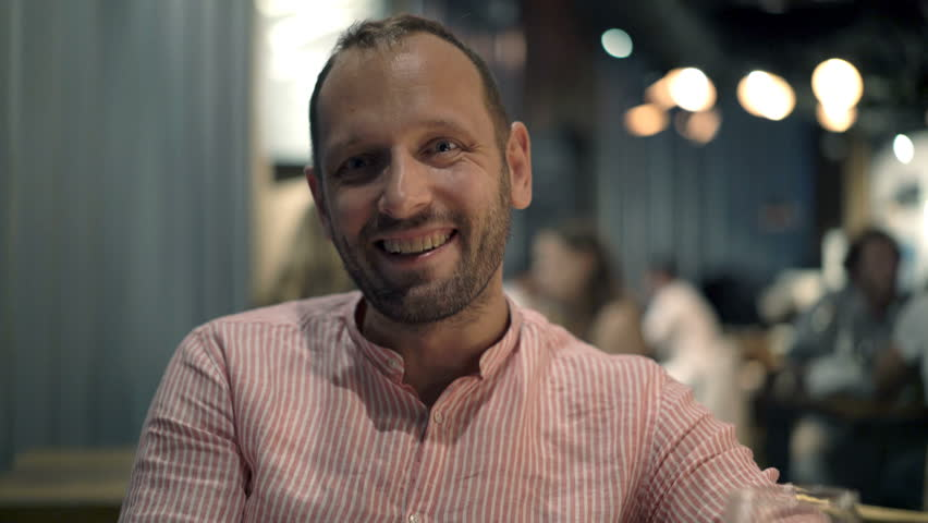 Portrait of happy, funny man talking to camera in cafe at night