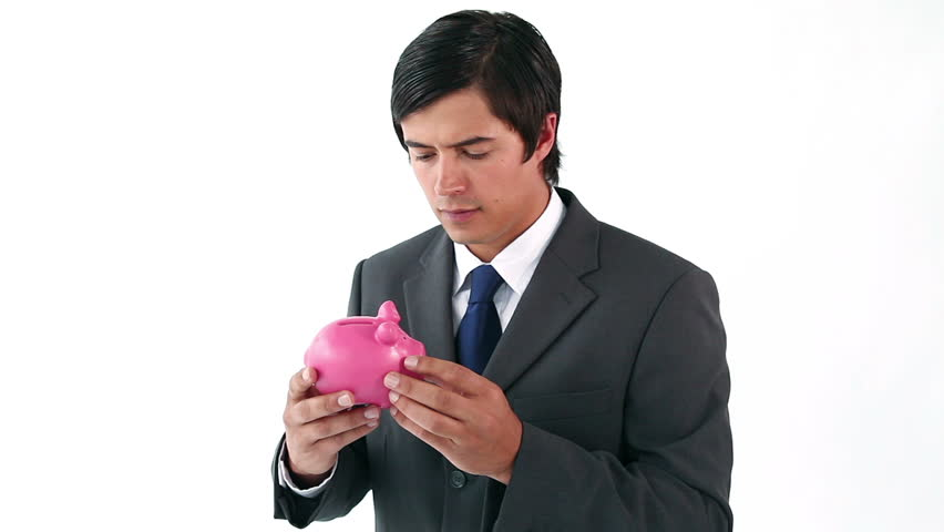 Businessman shaking his piggy bank against a white background