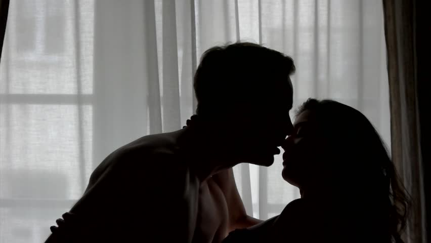 Kiss of couple in slow-mo. Silhouettes of man and woman. Nothing can break us apart. Passion and warmth of heart.
