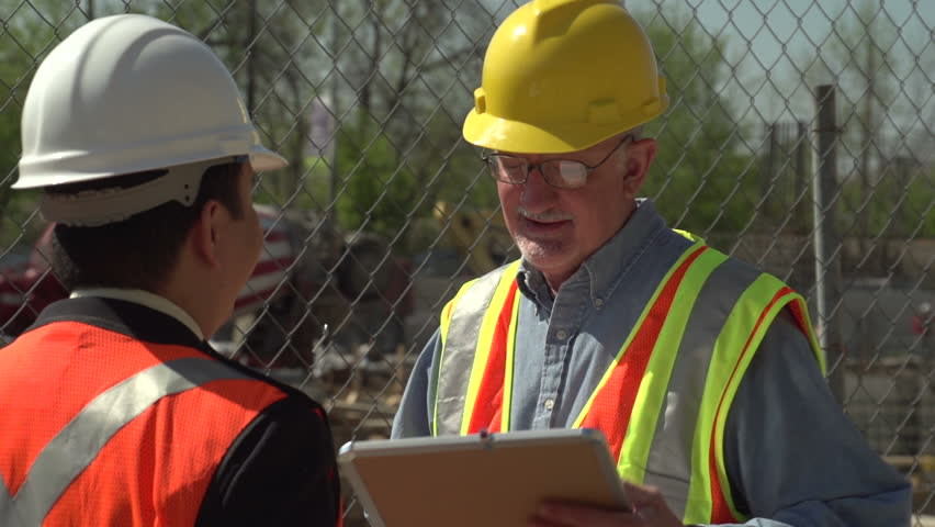 Construction worker and business man talking on site
