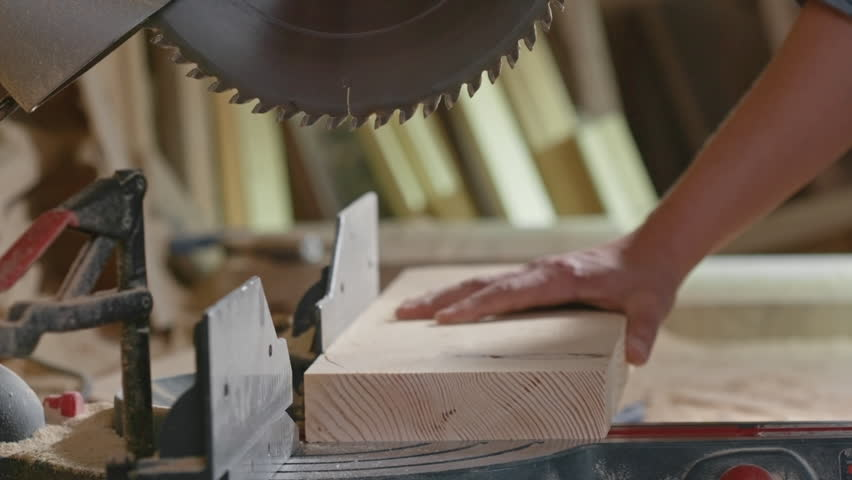 Male hands of carpenter holding wood plank on workbench and cutting it with sharp circular bandsaw | Shutterstock HD Video #22164139