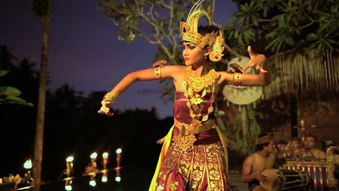 Balinese female artistic dancer performing in ceremonial traditional colorful costume using hands and fingers Indonesia South East Asia