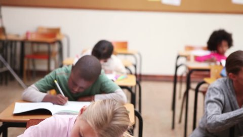 Serious pupils writing on their notebooks in the classroom - dolly shot