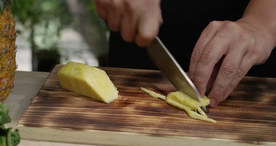 Chef chopping pineapple into strips