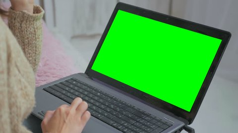 Woman using laptop with green screen. Business, communication, freelance and internet concept