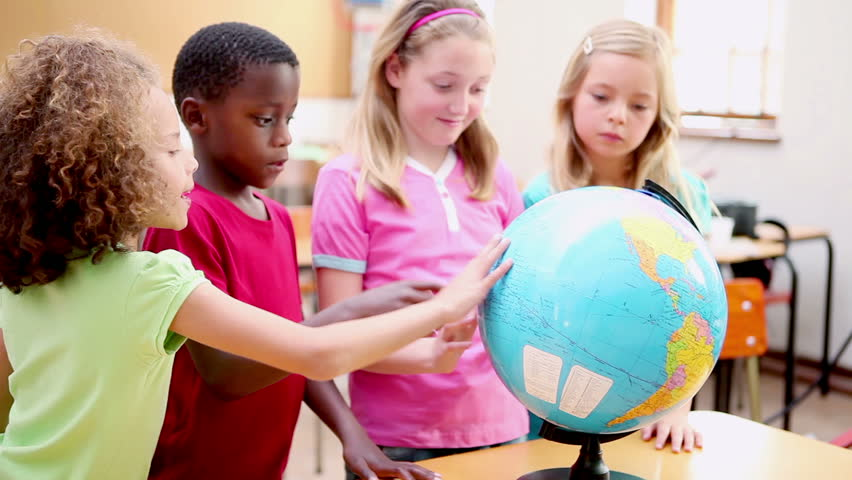 Smiling pupils looking at a globe in the classroom