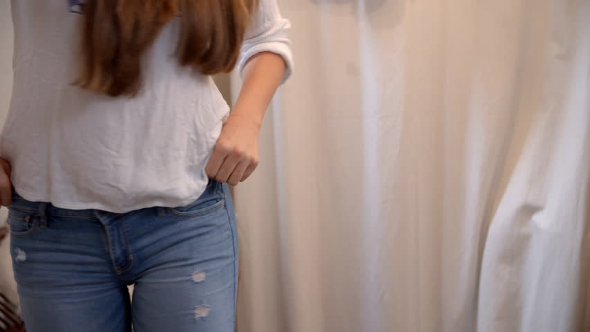 Woman trying on jeans in boutique changing room, mid section