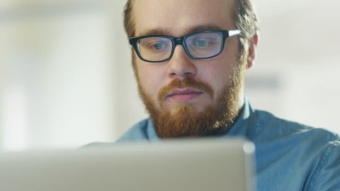 Portrait of a Bearded Young Man Wearing Glasses Sitting in His Office Working on a Computer. Computer Screen Reflects in His Glasses. Shot on RED Cinema Camera in 4K (UHD).