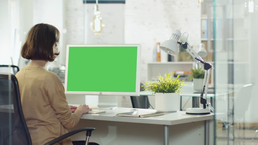 Creative Young Girl Works on Her Desktop Computer. Her Office/ Creative Studio is Brightly Lit. Computer Screen is Green Mock-up. Shot on RED Cinema Camera in 4K (UHD).