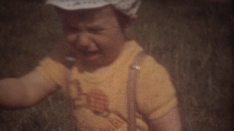 Family Chronicle: Little boy crying. Father shooting family video on 8mm camera