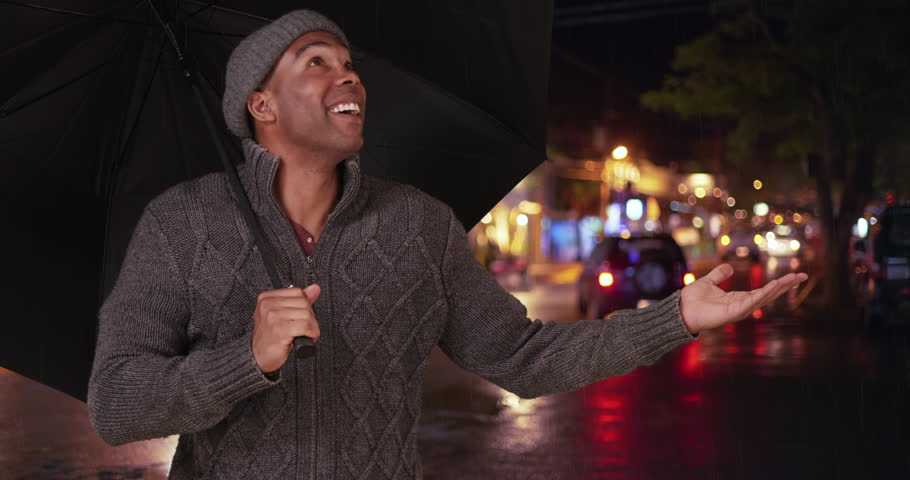 An African American man takes a selfie in the rain. A black guy takes a picture with his mobile phone with an umbrella in the city at night. 4k