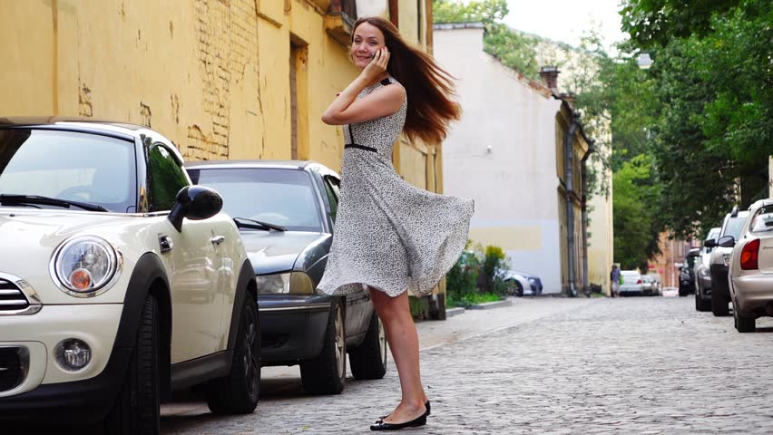 Woman talk on phone, stand alone at small street. Girl happily turn around, slow motion shot. Light dress fly in air when she slowly swing on place. Young adult person hang on phone while take walk