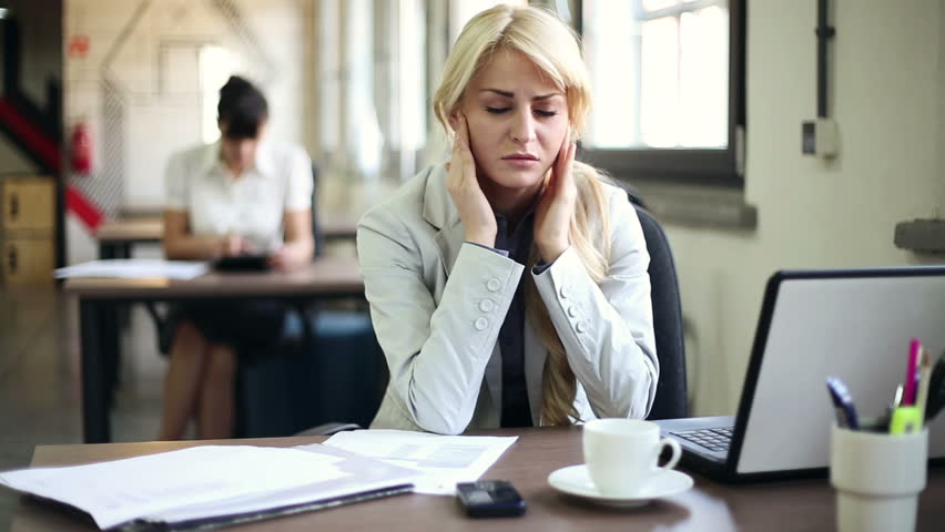 Young attractive businesswoman having headache in the office