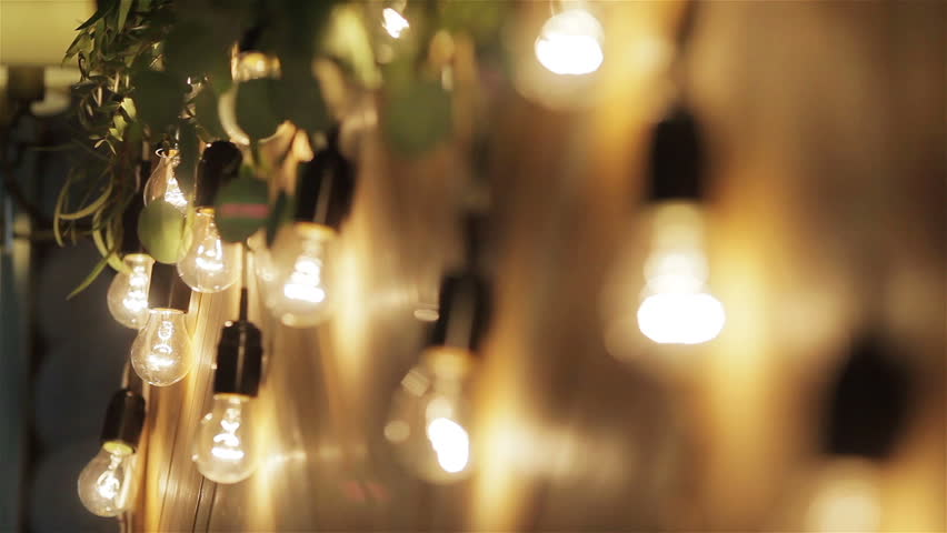 Light bulbs garland close up. Electric bulb shine hanging on wall as decoration for holiday close up rack focus macro