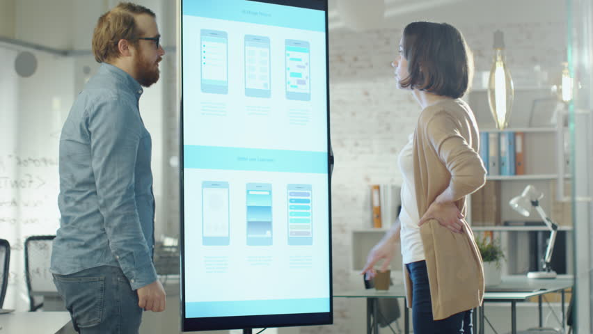 Young Coworkers Discuss Charts Drawn on Their Electronic Whiteboard. Their Office is Stylish and Modern Looking. Shot on RED Cinema Camera in 4K (UHD). | Shutterstock HD Video #22256347