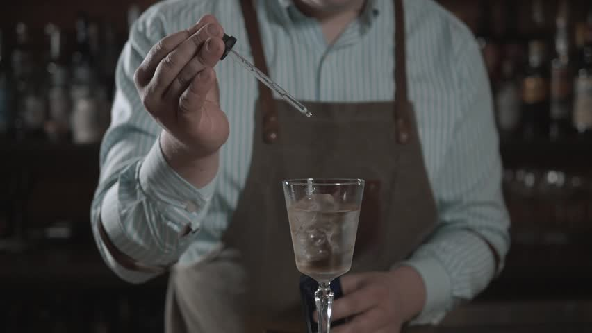bartender preparing cocktail with bar equipment, throw sieve and spray it