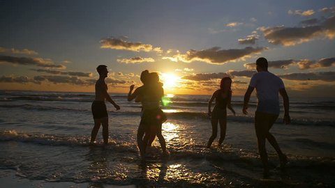 Group of people jumping dancing and having fun in the water on beach at sunset in slow motion